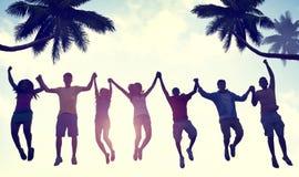Silhuetas dos povos que saltam pela praia Imagem de Stock