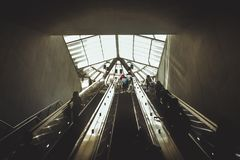 Silhuetas dos povos que vêm da escada rolante imagem de stock royalty free