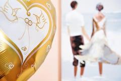 Silhuetas dos recém-casados na lua de mel e no balão festivo do ouro fotografia de stock royalty free