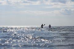 Silhuetas dos sunbathers que jogam no oceano fotografia de stock