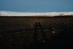 Silhuetas em uma praia preta da areia Imagem de Stock