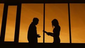 Silhuetas escuras da mulher magro e do homem que estão no perfil no crepúsculo perto da janela Esboço da mulher de negócios fêmea video estoque