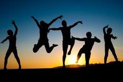 Silhuetas felizes dos miúdos que saltam na praia Imagens de Stock