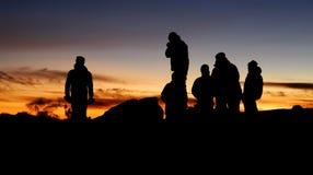 Silhuetas humanas no por do sol Fotografia de Stock