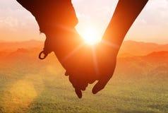 Silhuetas no por do sol dos pares loving que guardam as mãos quando walki Imagens de Stock