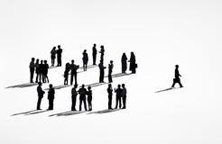 Silhuetas solitárias de um homem de negócio que anda longe do grupo Fotos de Stock Royalty Free