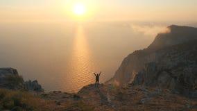 Silhuette av en ung kvinna beväpnar utsträckt observera en härlig dramatisk solnedgång ovanför ett hav från ett högt berg in lager videofilmer