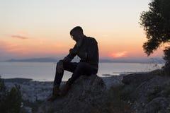 Silhuette d'un homme avec une barbe se reposant sur une roche photo libre de droits