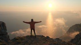 Silhuette del tramonto variopinto drammatico bello d'osservazione steso di armi del giovane sopra un mare da un'alta montagna video d archivio