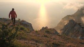 Silhuette młody człowiek zbroi szeroko rozpościerać obserwujący pięknego dramatycznego kolorowego zmierzch nad morze od wysokiej  zdjęcie wideo