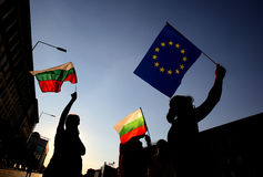 Silhuette of people holding Bulgarian and EU flags Stock Photos