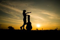 Silhuette of woman with guitar case Stock Images