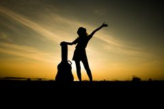 Silhuette of woman with guitar case Stock Photos