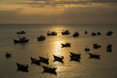 Silhuetted fishing boats during sunset Stock Photography