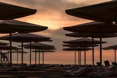 Silhuettes av stranddagdrivare och paraplyer på den tomma stranden i helgdagsafton Arkivfoton