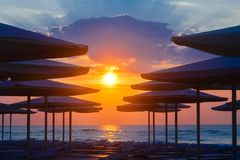 Beach loungers and umbrellas on a deserted beach in the evening. Silhuettes of beach loungers and umbrellas on a deserted beach in the evening on a sunset Royalty Free Stock Photos