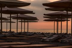 Silhuettes of beach loungers and umbrellas on empty beach in ev. Silhuettes of beach loungers and umbrellas on an empty beach in the evening on a sunset stock image