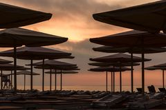 Silhuettes of beach loungers and umbrellas on empty beach in eve. Silhuettes of beach loungers and umbrellas on an empty beach in the evening on a sunset stock photos