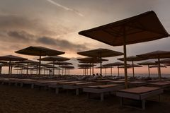 Silhuettes of beach loungers and umbrellas on empty beach in eve. Silhuettes of beach loungers and umbrellas on an empty beach in the evening on a sunset royalty free stock photos