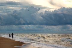 Silhuettes de la foto del makinf de dos personas del cielo dramático en un morni Foto de archivo