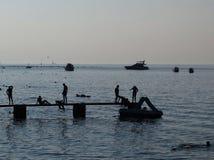 Silhuettes de la gente en la playa Imagen de archivo libre de regalías