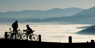 Silhuettes de los jinetes de la bicicleta de la montaña imagen de archivo libre de regalías