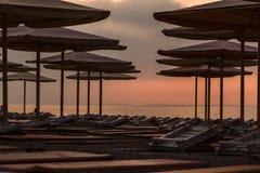 Silhuettes de los ociosos y de los paraguas de la playa en la playa vacía en ev Imagen de archivo
