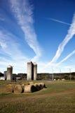 Sili dell'azienda agricola e balle di fieno con i contrails Fotografie Stock Libere da Diritti