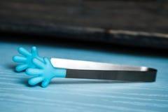 Silicio colorido, metal Sugar Tongs en fondo azul fotos de archivo libres de regalías