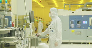 Silicon wafer manufacturing process in a clean room. Workers in a Clean room in a Semiconductor manufacturing facility stock footage