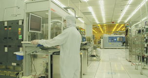 Silicon wafer manufacturing process in a clean room. Workers in a Clean room in a Semiconductor manufacturing facility