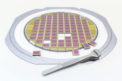 Silicon wafer with microchips, fixed in a holder with a steel frame on a gray background after the process of dicing. Microchip. Silicon wafer with microchips stock images