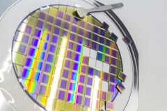 Silicon wafer with microchips, fixed in a holder with a steel frame on a gray background after the process of dicing. Microchip stock image