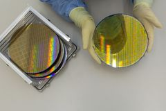 Free Silicon Wafers In Steel Holder Box Take Out By Hand In Gloves- A Wafer Is A Thin Slice Of Semiconductor Material, Such Royalty Free Stock Photos - 137107938
