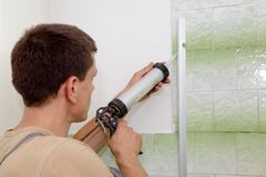 Silicone. Plumber using silicone cartridge for fixing aluminum batten of shower cabin stock photos