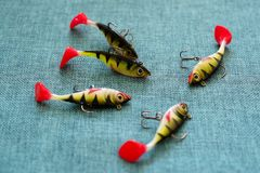 Silicone bait. Twisters on the background of burlap. Lures with treble hooks in the form of small perch. stock image