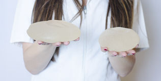 Silicone breast implants. Nurse holding implants. Doctor holding implants. Plastic surgery Stock Photos