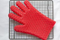 Silicone glove. Red silicone glove on cooling tray Stock Image