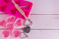 Silicone molds for baking in the form of heart and tools for bak. Ing cookies, muffins and cake on a white wooden background Stock Photo