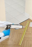 Silicone sealant gun glue strip between wooden floor and tiles Stock Image