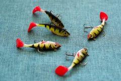 Siliconeaas Twisters op de achtergrond van jute Lokmiddelen met drievoudige haken in de vorm van kleine toppositie stock afbeelding