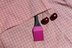 Silikonbürste und Kirsche zwei auf rosa Gitter Stoff Stockfotos