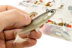Silikonfisk för pik i händerna av fiskaren på fisketillbehörbakgrunden Royaltyfri Fotografi