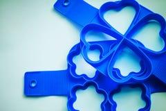 Silikonherz, Blumen formen Formen auf blauem Hintergrund Werkzeug für das Backen von Plätzchen, puncakes, Eier Silikonformen für  Stockfoto