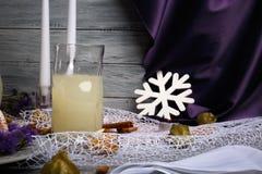 Silk фиолетовый занавес, 2 горящих свечи, белая снежинка, торт на свете - серая предпосылка кольца Стоковое Изображение