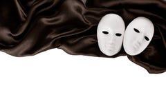 Белые маски и черная silk ткань Стоковое Фото