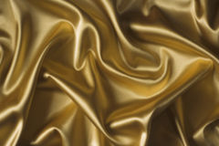 Silk background. Textile yellow silk backround draped in waves royalty free stock photography