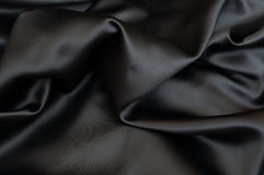 Silk Background. Black Texture - Dark Wavy Glossy Silk Drapery - Shallow Depth of Field royalty free stock photography