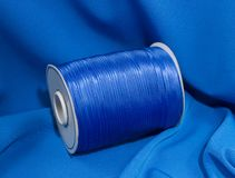 Silk blue braid for sewing on blue fabric. Composition stock photography