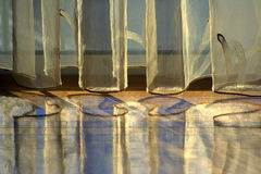 Silk curtains reflected on wooden floor.. Silk curtains reflected on wooden floor give off a shimmering pattern. Horizontal orientation Royalty Free Stock Image